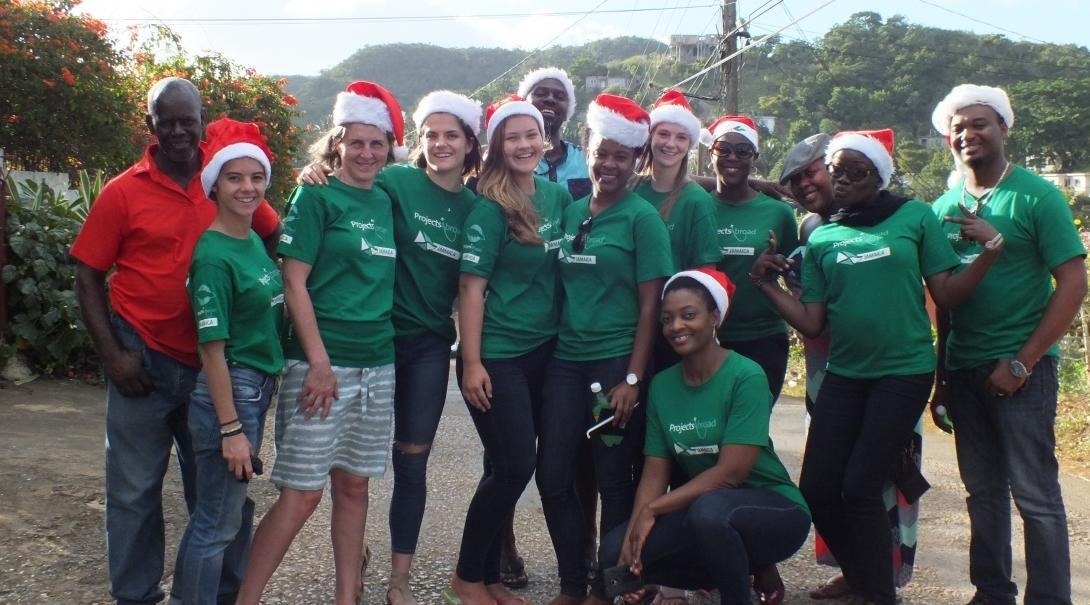 Volunteers working with children at a Summer Camp in Jamaica, take a photo with their supervisors outside their placement.